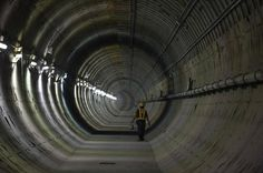 "This picture taken on March 8, 2016 shows a worker walking in a tunnel under construction along the current extension of the Metropolitan Rapid Transit (MRT) subway ""Blue Line"" into Bangkok's historic district of Chinatown. The Blue Line is the MRT's only line currently in operation, running from the central Hua Lamphong train station to the north of Bangkok and was opened in 2004 as Bangkok's second public transit system. The MRT serves hundreds of thousands of passengers each day…"