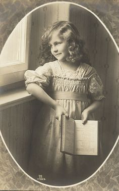 Pretty little girl at window, holding book, vintage photo