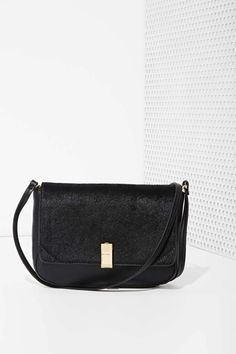 This black leather bag by IIIBeCa has a pony hair foldover flap, gold hardware, and removable shoulder strap.
