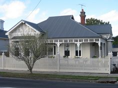 This wonderful concoction of Arts and Crafts timber fretwork, gabled return verandah and complex rooflines of red tiles at varying angles appear on a grand weatherbaord Edwardian villa built in the Melbourne suburb of Moonee Ponds. Standing proudly