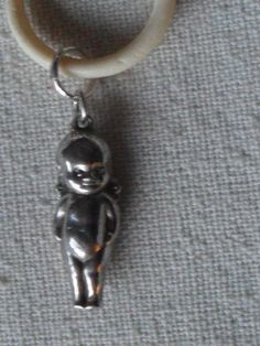 Antique Continental Silver Charm of a Kewpie Baby Doll on a bone teething ring