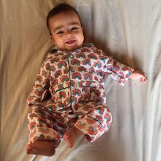 """""""Baby's who love us, and Babies we Love! Precious A wearing one of our Tropics pajamas- all hand block printed in organic cottons. A favorite product of…"""""""