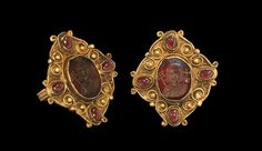 BYZANTINE GOLD FIGURAL INTAGLIO RING Circa 6th-8th century AD. A gold finger ring comprising a flat hoop with filigree border and large lozengiform bezel; the edges scrolled with filigree wire edging enclosing twelve large granules and four cabochon garnets; the central feature a garnet intaglio set en cloison; the intaglio formed as a bearded male bust with decorated tunic flanked by a vexillum and orb-with-cross, and with a cross clechee above the head. Gold and garnet,
