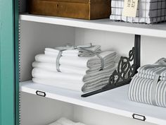 Iron brackets attached to shelves help to keep stacks of towels or sheets neat and tidy. Labeling the fronts of the shelves takes the guess work out of what size sheets are in the stacks.