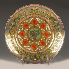 A Russian porcelain dessert plate from the Kremlin Service, made by the Imperial Porcelain Factory during the reign of Tsar Nicholas I. The center of the cavetto is painted with a black double-headed Imperial Eagle with crown, orb and scepter and surrounded by a gilt band inscribed 'Nicholas the Emperor and Ruler of all the Russias'. The elaborate border is decorated with blue and green flowers against a burnished gilt ground.