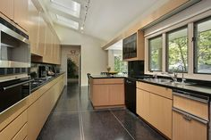 Modern wood kitchen with sloping white ceiling, skylights and dark floor.
