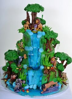 Pastry Palace Las Vegas - Kid's Cake #832 – Lion King Pride Lands. Simba and Nala surrounded by lush greenery, trees and a cascading blue waterfall.