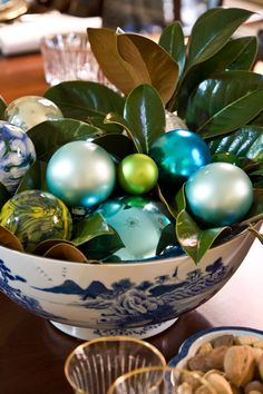Pretty antique bowl filled with magnolia leaves,glass painted balls, and holiday ornaments make a simple but elegant centerpiece