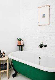 Bathroom with exposed brick wall and green freestanding bath tub