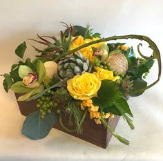 Large Texture Box with roses, succulents, viburnum berries, cymbidium orchids, tillandsia, kalanchoe, eucalyptus pods, tree ivy, contorted willow, and reindeer moss in a wooden box.