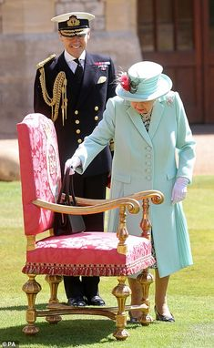 The Queen places her handbag on a chair before presenting Captain Sir Thomas Moore with hi...