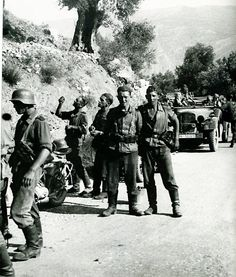 """Invading German motorized troops pause for a break somewhere in the mountain roads of Greece, April 1941. The Greeks put up a stiff fight but were overwhelmed by superior numbers and weapons. The Greek capital, Athens, was occupied at the end of April after being declared an """"open city."""""""