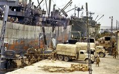 A GMC353 front, Bedford QL centre and CMP Chevrolet/Ford C/F60L rear - Allied ships unloading supplies Sfax, Tunisia, 1943