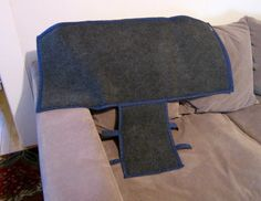 This is a completed adjustable arm cover for couch or chair. The base material is navy blue quilted fabric, trimmed with blue dot matching cotton trim. The front arm flap is secured to the rest of the arm cover using velcro tabs that can be adjusted to snug the cover tightly to the arm. The flat mat portion is 42 inches long by 18 inches wide. The front arm flap is 15 inches long by 10 inches wide. This mat is designed to adapt to a variety of arm widths, as long as the front width is no…
