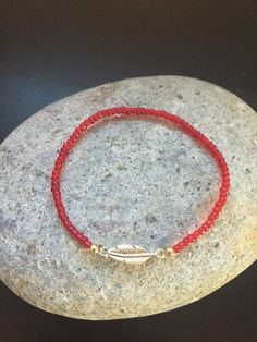 Thin Red Bead Gold Feather Stretch Bracelet by Kosmikchic on Etsy