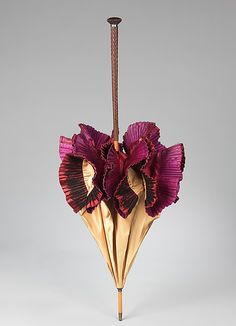 Parasol, Lyon, 1890-99. The parasol featured here captures the essence of the 1890s with its gay color combination and exuberant lace-covered ruffle at the hem. The detailing of the handle is very engaging. Also, the color combination of the garnet ruffle and the purple lining is indicative of the period and a typical French touch.
