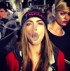 "eyebrows & attitude - fashion ""it"" girl of the moment, Cara Delevingne, blowing smoke backstage at a fashion show"