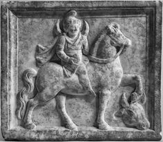 "Votive relief from Asia Minor (2nd century AD) - Mên, the moon god of Asia Minor, wears a ""Phrygian"" cap and a traveller's costume. A crescent moon appears over his shoulders. He holds a pine cone in his right hand. The head of a sacrificial animal lies beneath the horse's hoof."