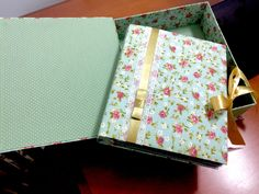 Álbum e caixa de cartonagem revestidos em tecido poá e floral.