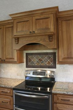 Small traditional corbels add just the right amount of interest to this arched valance range hood with mantle shelf.