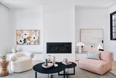 A timeless lifestyle sanctuary for a vibrant young family. James Hardie Paneling above fireplace, Illusion Gas Log Fireplace, @kimmyhoganloves Artwork (left of fireplace), Tracy Mock Artwork (right of fireplace), @hkliving Living White Vases and Lamp, @globewest Occasional Chairs, @armadilloandco Rug, @therugcollection Black Coffee Tables, all books, small vessels and accessories from Norsu Interiors.