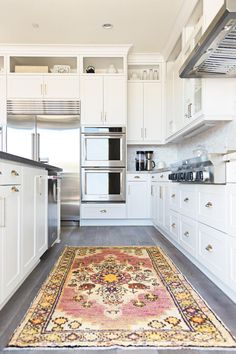 All-white+cabinets+paired+with+stainless+steel+appliances+creates+a+clean,+classic+look+for+this+kitchen.+Gray+wood+floors+and+a+colorful+rug+complete+the+design.