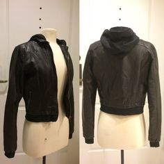 """Cropped Faux Leather hoodie jacket Black faux leather bomber style jacket with the look of a hoodie underneath. Has two small functional zippered pockets on the front. Brass hardware. This has been Preloved but still has a lot of life left in it. Last photo shows wear on inside of the jacket at the shoulders and on the right sleeve. Exterior made of 70% pvc 30% polyurethane. Lining 100% polyester. Bust 17.5"""". Length 19"""". Junior sized medium. Would perfectly fit a women's small or extra small…"""