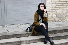 Elisa from the Fashion- and Lifestyleblog www.schwarzersamt.com shows a cozy autumn look with a woolen green cardigan from Primark, a beige sweater, a big black scarf from TOPSHOP, a black high waist jeans from Weekday and VAGABOND chelsea boots . It's a perfect look for the colder autumn days during November