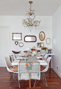 A sala de jantar da designer Ana Morelli tem paredes e móveis brancos, mas está longe de ser um ambiente neutro. Ele ganhou charme com vários espelhos, bules com flores e xícaras coloridas