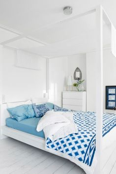 View of MALM bed, painted white with blue and white textiles.