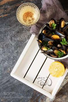 Mussels with herbs in a bowl with lemon and wine on a white wood by ngaus from http://500px.com/photo/215325329 - Mussels with herbs in a bowl with lemon and wine on a white wooden board. Seafood. Food at the shore of the French Sea. Dark background. More on dokonow.com.