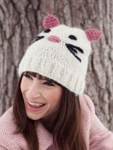 Catarina is a precious knit hat featuring an embroidered face and knitted ears.