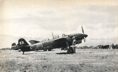 """Yokosuka D4Y1-C type 2 reconnaissance aircraft Suisei """"Judy"""" seen at Lakunai airfield during 1943.In background is Mitsubishi G3M1-L of 251.kokutai (UI-902) used as transport plane in the unit."""