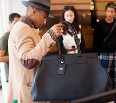 Pharrell Williams e sua bolsa giga Moynat personalizada com suas inicias durante uma visita ao ateliê da marca (Foto: Divulgação)