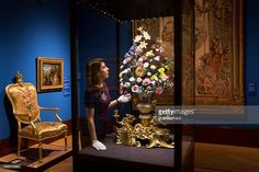 A member of the gallery staff views 'The Sunflower Clock', created by the Vincennes porcelain factory in 1752, at The Queen's Gallery on March 19, 2015 in London, England. The 'Painting Paradise: The Art of the Garden' exhibition opens this week and features over 150 works from the Royal Collection, inspired by royal gardens and dating from the 16th through to the early 20th century.