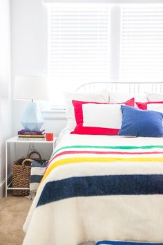 My all white bedroom at Carlton Landing (our lake house on Lake Eufaula)  complete with a Hudson Bay Point blanket in a happy colorful stripe.  www.pencilshavingsstudio.com