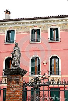 Photo made at the entrance of a house in Breganze in the province of Vicenza in Veneto (Italy). In the picture you see, in the foreground, the entrance gate with a column that supports brick and a statue of woman. Beyond the gate, and the branches of a small tree you see the facade of the office villa now a restaurant.