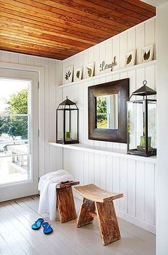 The entry features a pair of wall length floating shelves. The upper shelf is adorned with framed pressed leaves. The lower shelf holds a pair of large candle lanterns flanking a chunky wood framed square mirror. A pair of reclaimed wood zen stools stand below the shelves. A glass door allows light to flood into the entryway.