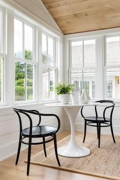 Black bistro chairs sit on a bound sisal rug at a white Saarinen Table. Rattan Dining Chairs, Bistro Chairs, Cafe Chairs, Small Sunroom, Sunroom Dining, Sunroom Office, Dining Rooms, Saarinen Table, Sunroom Decorating