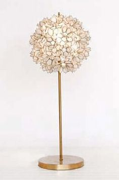 """Description: Add a captivating explosion of light in your space with the Venus Table Lamp from Worlds Away! Featured in a round floral design of capiz shells, this modern accessory instantly adds light and color in areas where both are needed.  $465 28"""" high x 12"""" diameter"""