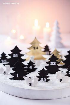 Buddel-Adventskalender mit Kunstschnee: Schneelandschaft in Weiß und Gold mit Tannenbäumen und Porzellanfiguren