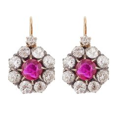 Victorian Ruby Silver Diamond Gold Rosette Earrings. Each earring is backed in 18 karat gold, topped in silver and centers 1 prong-set round mixed-cut *NON HEAT-TREATED BURMA ruby, surrounded by 8 old European-cut diamonds and suspended from 1 smaller old European-cut diamond, completed by a 14 karat gold wire and lever back.