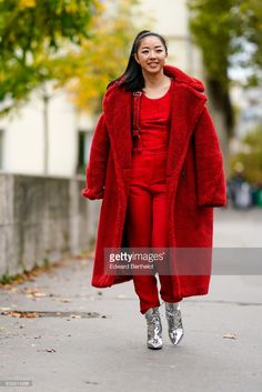 Yuwei Zhangzou wears a red fluffy coat, a red top, red pants, silver shoes, outside Shiatzy Chen, during Paris Fashion Week Womenswear Spring/Summer 2018, on October 2, 2017 in Paris, France.