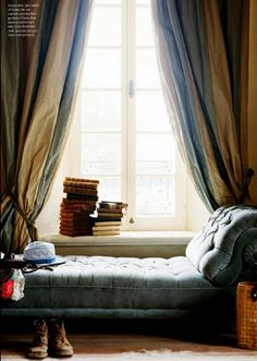Nice reading place, chair, and big window with curtains.