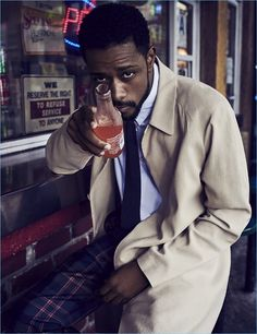 Enjoying a drink, Lakeith Stanfield wears a Bottega Veneta coat with a shirt and tie by Margaret Howell. He also rocks Louis Vuitton check trousers.