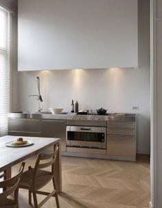 Moderne rvs keukenfronten en strakke #schouw ombouw met klassieke #visgraatvloer