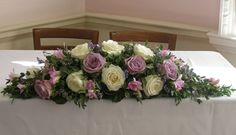ceremony table flower arrangement of ivory Avalanch roses, dusky lilac roses, Memory Lane, freesias, and limonium...gives a very vintage vibe