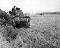 A British Sherman tank links up with British Airborne forces after having moved inland from the beaches of Normandy. The original caption states this tank was engaging German troops that had been using the Horsa Gliders as cover.