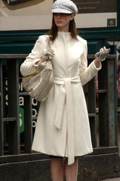 Anne Hathaway in Devil Wears Prada. Anne's strappy shoes in this scene were designed by Marni, she wears an Ivory Angora Coat from Yigal Azrouel, her hat and gloves are Chanel. The purse she carries, a Calvin Klein Gold Python Hobo bag, completes this fashion look from the film.