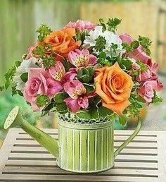 Regadera de metal conbflores de temporada asi como astromelia rosas y clavel